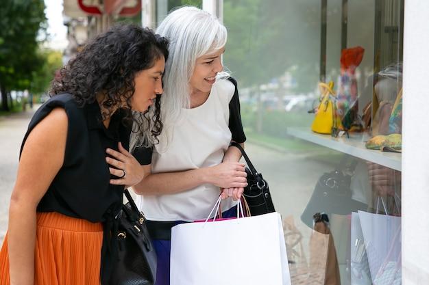 쇼핑 가방을 들고 외부 상점에 서서 상점 창에서 액세서리를 쳐다보고 흥분된 여자 친구. 측면보기. 윈도우 쇼핑 개념