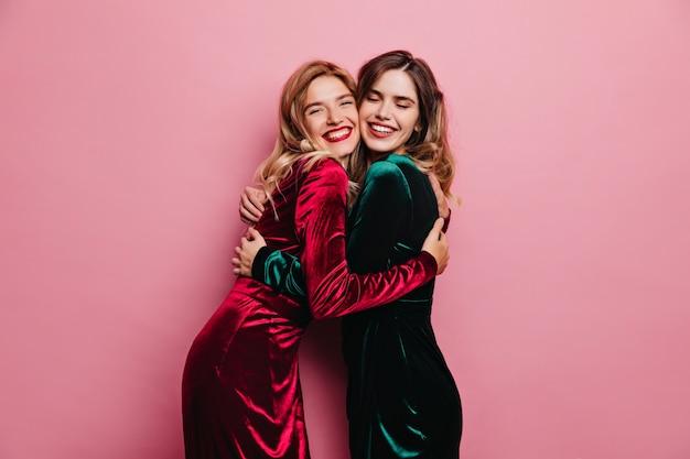흥분된 여자 친구는 분홍색 벽에 포옹. 미소로 포즈를 취하는 blithesome 성인 자매의 실내 사진.