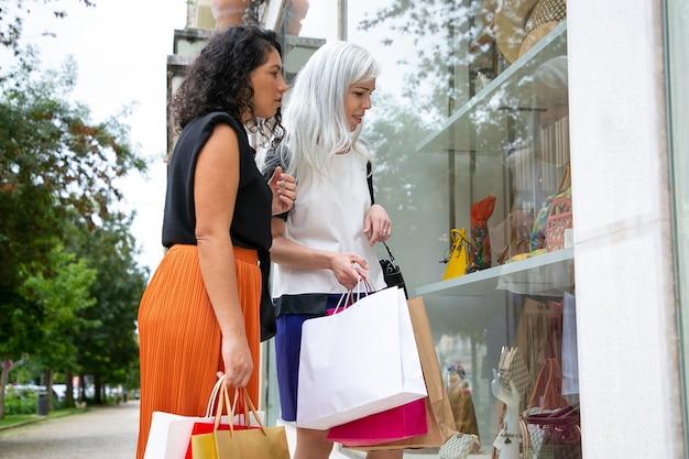 Взволнованные подруги смотрят на аксессуары в витрине магазина, держат сумки и стоят в магазине снаружи. вид сбоку. концепция магазина окон