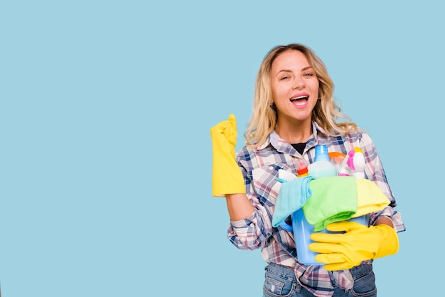 Excited female housekeeper holding bucket with cleaning products while clenching her fist over colored background