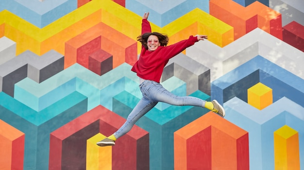 Возбужденная женщина прыгает против стены граффити