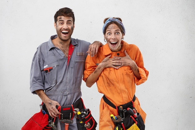 Excited female and male plumbers don`t believe their eyes, look with widely opened mouthes