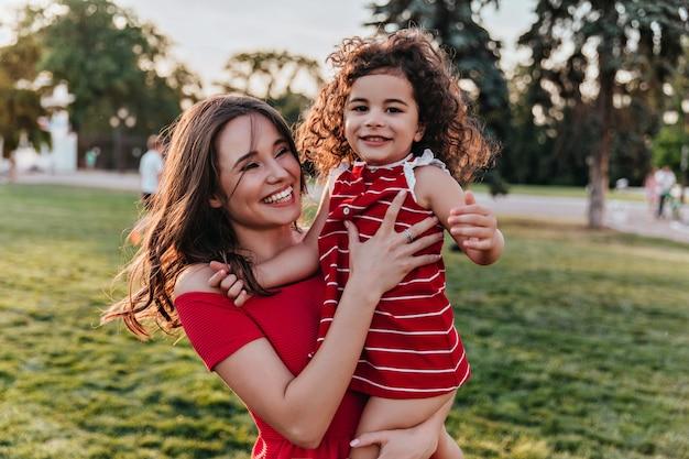 Eccitato modello femminile che tiene la bambina e sorridente sulla natura foto all'aperto di spettacolare donna bianca scherzare con la figlia durante il riposo nel parco.