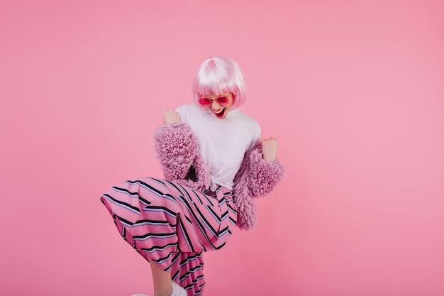 ポジティブな感情を表現するピンクの服を着た興奮した女性モデル。幸せな笑顔で短い明るいperuke面白いダンスで洗練された女の子