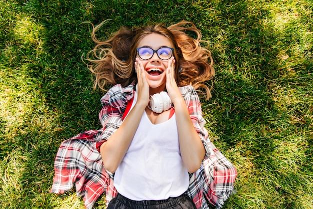 公園の芝生の上に横たわっている興奮した女性モデル。屋外で休んでいるヘッドフォンの壮大な白人の女の子。