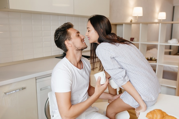 Excited female model sits on table kissing man in white t-shirt, enjoying good morning