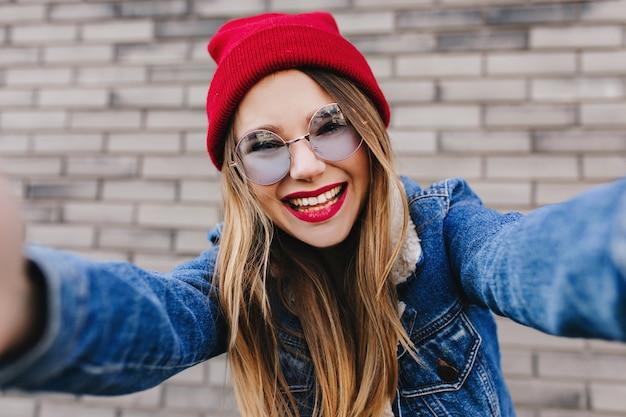 Modello femminile eccitato indossa il cappello rosso che fa selfie sul muro di mattoni. ragazza bianca che ride in occhiali da sole e giacca di jeans in posa vicino al muro.