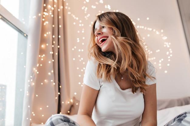 그녀의 방에서 웃고 트렌디 한 헤어 스타일로 흥분된 여성 모델. 집에 앉아있는 동안 아침을 즐기는 사랑스러운 백인 여자의 실내 샷.