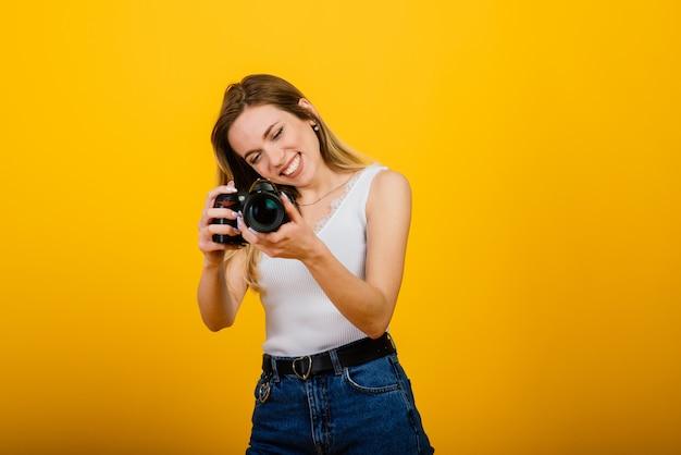 Excited женский фотограф работая в студии. портрет потрясающей блондинки с фотоаппаратом.