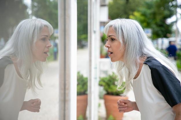 Возбужденная женщина-шопоголик смотрит в витрину магазина с открытым ртом, стоя у магазина снаружи. вид сбоку. концепция магазина окон