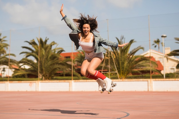A excited female skater jumping over the outdoor court