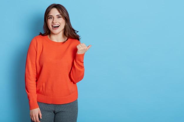 Возбужденная женщина в оранжевом свитере указывая в сторону с счастливым выражением лица, изолированным над синей стеной.