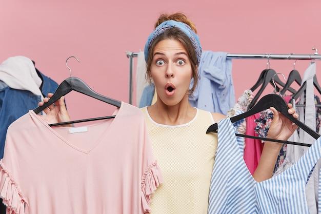 머리에 스카프를 착용하는 흥분된 여성, 눈이 아프고 턱을 보면서 두 손에 드레스가있는 두 개의 옷걸이를 들고 저렴한 가격과 높은 품질의 옷에 놀라게되었습니다.