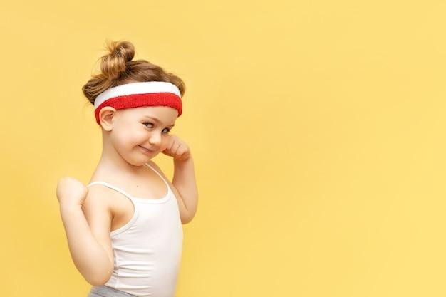 黄色の壁の上の赤いヘッドバンドでポーズをとって興奮したフィットネスの子供の女の子