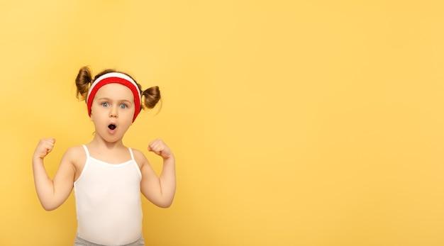 黄色の壁の上のスポーツウェアのヘッドバンドでポーズをとる興奮したフィットネスの子供。