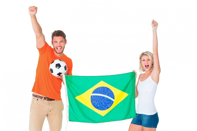 Excited football fan couple holding brazil flag