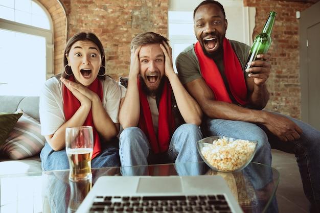 집에서 스포츠 경기를 보는 흥분한 축구 팬, 코로나바이러스 전염병 발생 동안 좋아하는 팀의 원격 지원. 온라인 스트리밍, 인간의 감정을 경기장으로 번역합니다. 스포츠, 안전.