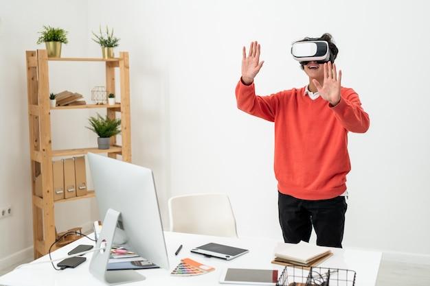 Взволнованный фрилансер в повседневной одежде и гарнитуре виртуальной реальности трогает виртуальный дисплей, одновременно переживая другую реальность