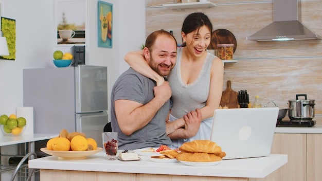 Excited freelancer working from home on laptop after reading a good news. successful overjoyed euphoric entrepreneur at home in the morning, winner and business triumph