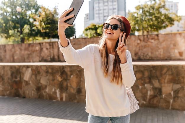 自撮りをする長い髪型の興奮したフランスの女の子。スマートフォンでポーズをとる壮大な笑う女性の屋外写真。