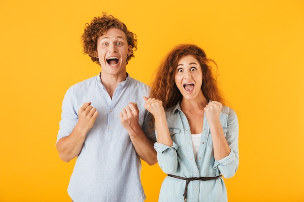 Excited friends loving couple showing winner gesture.