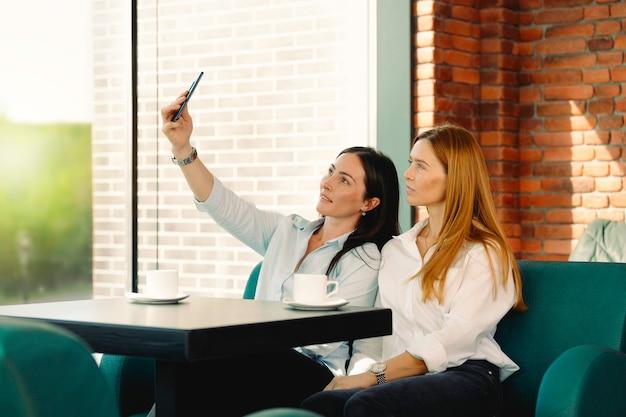 ワクワクする友達がスマホで自分撮りをしてコーヒーショップで楽しんでいます。学生たちはカフェで集まった電話で写真に微笑む。オフィスのコーヒーブレイクで自画像のポーズをとる2人の若いビジネスウーマン。