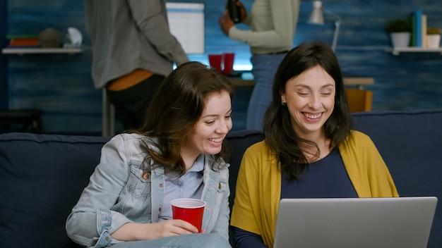 Amici eccitati che guardano lo spettacolo di intrattenimento sul laptop mentre sono seduti sul divano in soggiorno a tarda notte durante la festa. donna africana con un amico che beve birra, ballando insieme godendosi il tempo libero