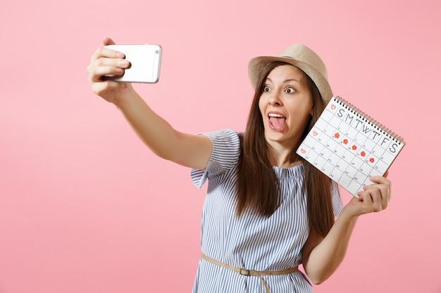 Возбужденная веселая женщина в синем платье делает селфи на мобильном телефоне, держа календарь периодов для проверки дней менструации, изолированных на розовом фоне. медицинское здравоохранение, гинекологическая концепция. копировать пространство