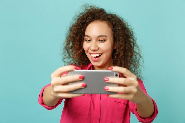 Ragazza africana divertente emozionante in vestiti casuali rosa che fanno selfie sparato sul telefono cellulare isolato sul fondo blu della parete del turchese in studio. concetto di stile di vita di emozioni sincere della gente. mock up copia spazio.