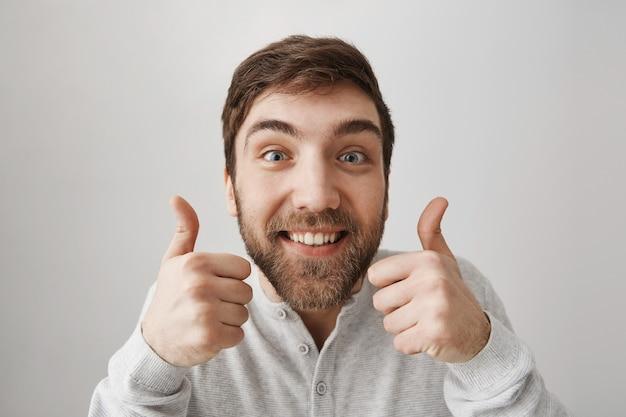Ragazzo barbuto divertente emozionante che mostra il pollice in su in approvazione