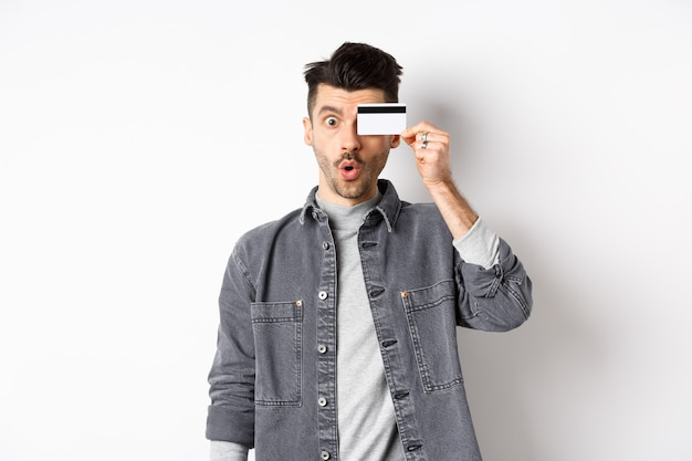 Excited funny man hold plastic credit card on eye and say wow, checking out special deal, standing on white background.