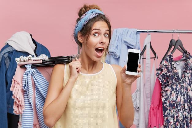 여름 옷 옷걸이를 들고 스마트 폰을 시연하는 흥분된 재미있는 여자 shopaholic