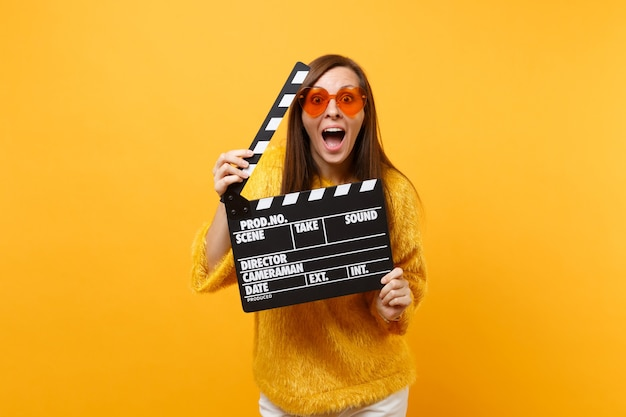 黄色の背景で隔離のカチンコを作る古典的な黒いフィルムを保持している毛皮のセーターとオレンジ色のハートの眼鏡で興奮した面白い若い女性。人々は誠実な感情、ライフスタイル。広告エリア。