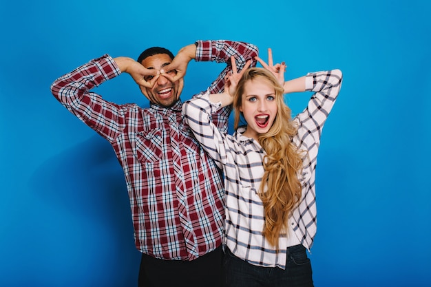 Excited funny young woman with long blonde hair having fun with handsome guy fooling around together. expressing true brightful positive emotions, smiling, free time.