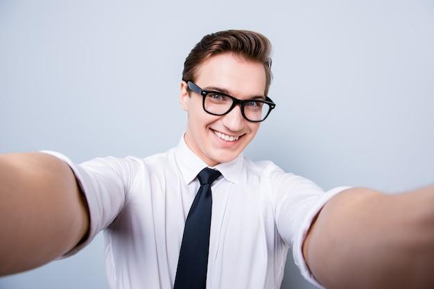 トレンディなメガネとフォーマルウェアの興奮したオタクの若い男は、カメラで自分撮りを撮影し、純粋な空間に立って、親指を立てるサインを見せて、笑っています