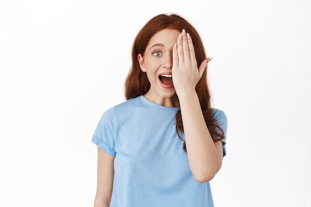Возбужденная рыжая кудрявая девушка, закинувшая половину лица и кричащая от радости, уставилась на удивительное классное пространство для копирования продукта, стоящее на белом
