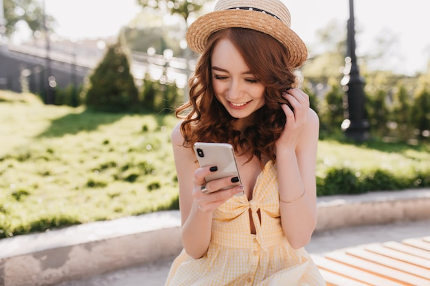 Excited ginger girl in hat texting message with smile. outdoor portrait of sensual red-haired lady posing with her smartphone in park.
