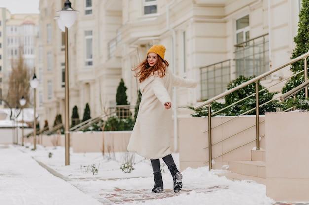 Взволнованная рыжая девушка смотрит через плечо во время прогулки по заснеженной улице. открытый выстрел очаровательной рыжеволосой женщины в белом халате.