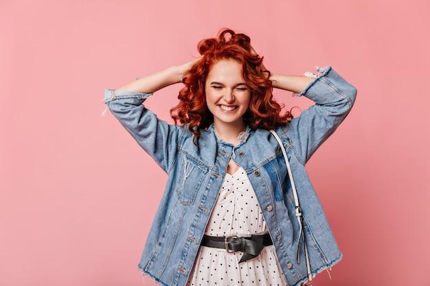 Взволнованная рыжая девушка улыбается с закрытыми глазами на розовом фоне. вид спереди блаженной женщины в джинсовой куртке, касающейся вьющихся волос.