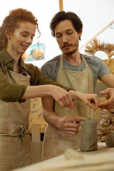 興奮した女の子。彼女の動きとテクニックをマスターしながら新鮮な粘土で作業する陽気な若い女性