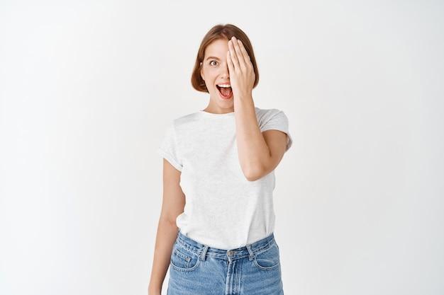 Ragazza eccitata copre metà del viso e degli occhi, ansimando stupita e guardando qualcosa di fantastico, in piedi in maglietta e jeans sul muro bianco