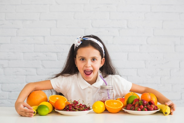 Excited girl covering the colorful fresh organic fruits
