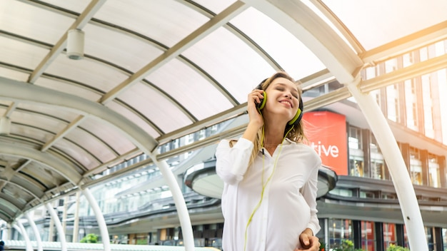 Excited girl dancing and listening music with headphones in the street with happiness