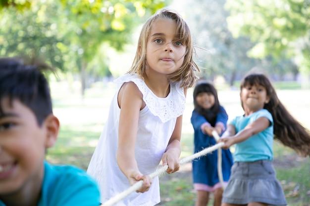 Взволнованная девушка наслаждается активным отдыхом с одноклассниками, играет с друзьями в перетягивание каната. группа детей, весело проводящих время в парке. концепция детства