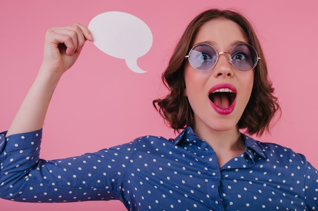 ピンクの壁に不安を表現する興奮した女の子。何かを考えている魅力的なブルネットの若い女性。