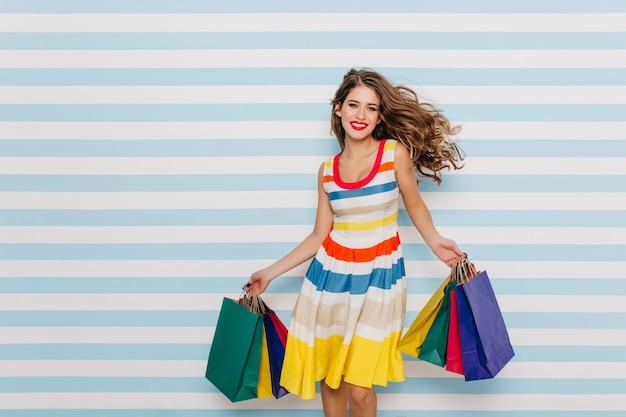 Возбужденная девушка смешно танцует на синей полосатой стене. внутреннее фото веселой дамы, наслаждающейся продажами во время покупок.