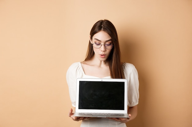 Excited girl in glasses show laptop screen, demonstrate online offer on computer, standing against beige background.