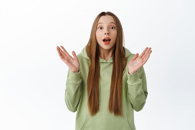 흥분한 소녀는 놀라운 소식을 듣고 매료되어 손뼉을 치고 놀란 얼굴로 박수를 치고 멋진 것을 확인하고 감동을 받은 흰 벽에 서 있습니다