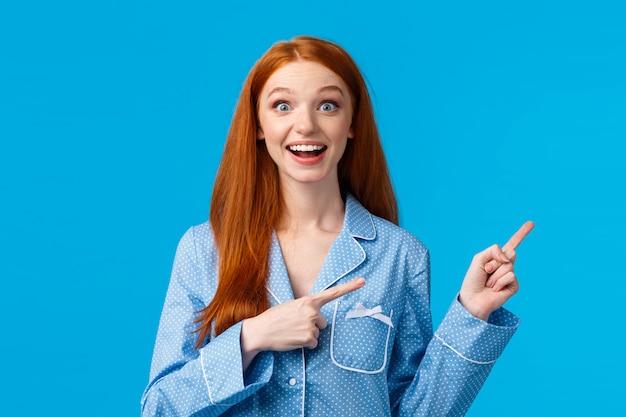Возбужденная девушка слышит замечательные новости, специальные скидки на курортный сезон. привлекательная рыжая девушка-подросток в ночном белье улыбается с удивлением и восторгом, указывая в верхнем правом углу, синяя стена