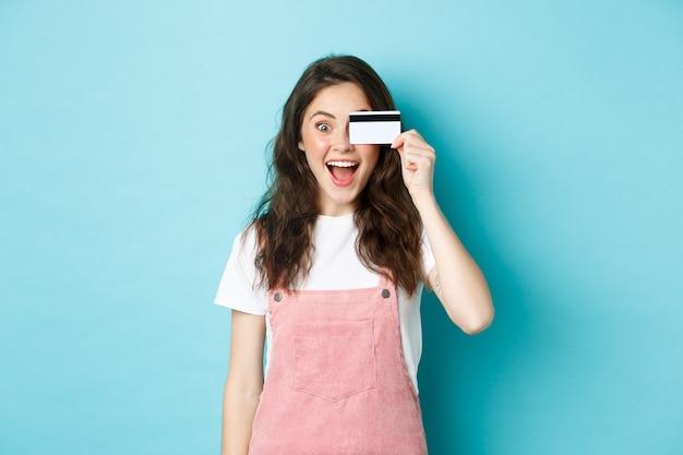 Возбужденная девушка держит пластиковую кредитную карту возле глаза и изумленно смотрит в камеру, покупает вещи в магазине, идет по магазинам, тратит деньги на банковский счет, стоит на синем фоне.